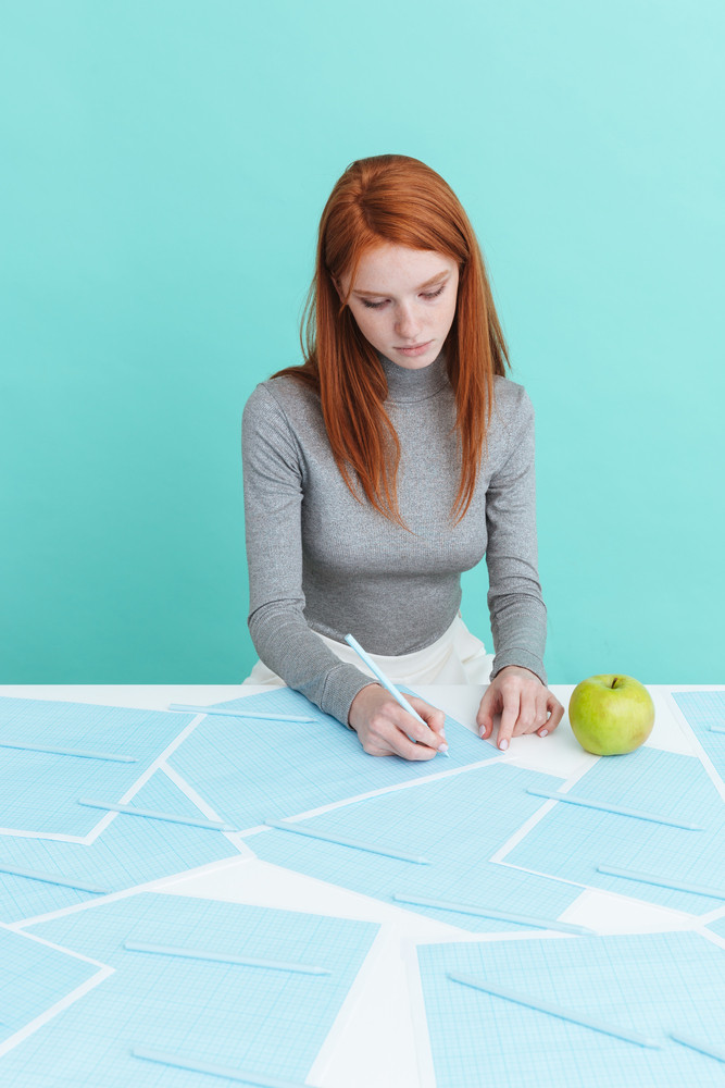 Attractive young woman with green apple sitting and writing at the table over blue background