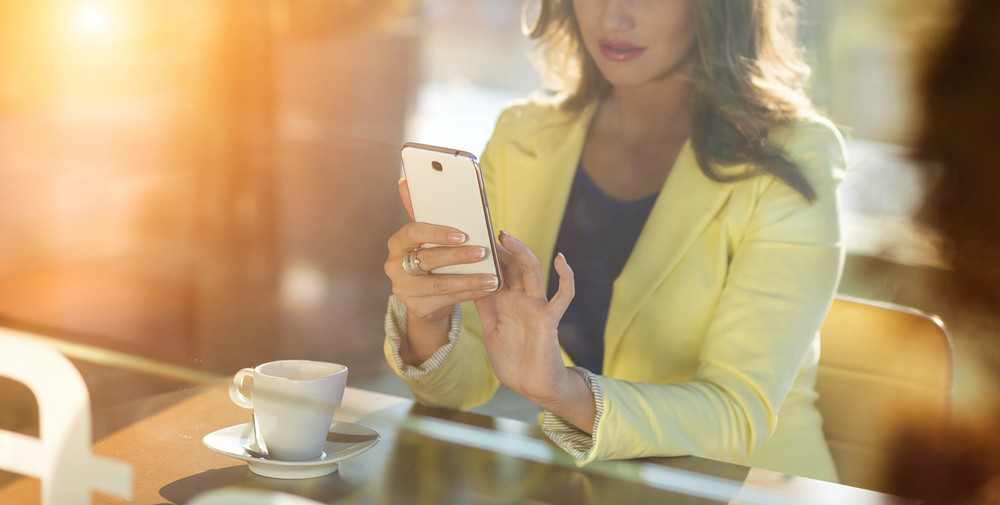 Attractive young woman with smart phone in a cafe