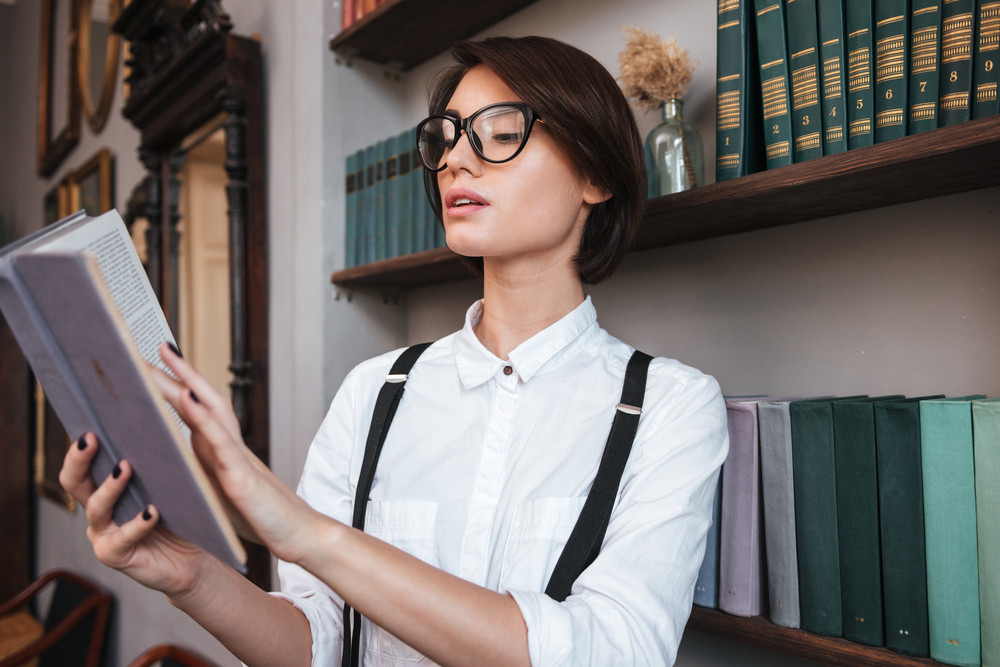 Authoress in glasses and shirt reading book near the bookshelf