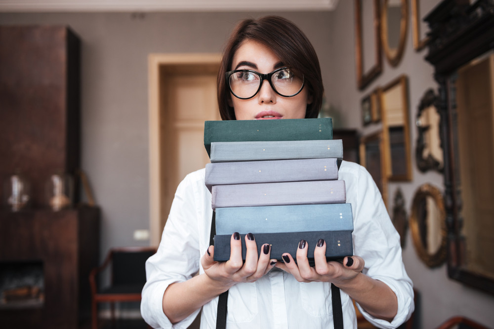 Authoress in glasses and white shirt holding books and looking away