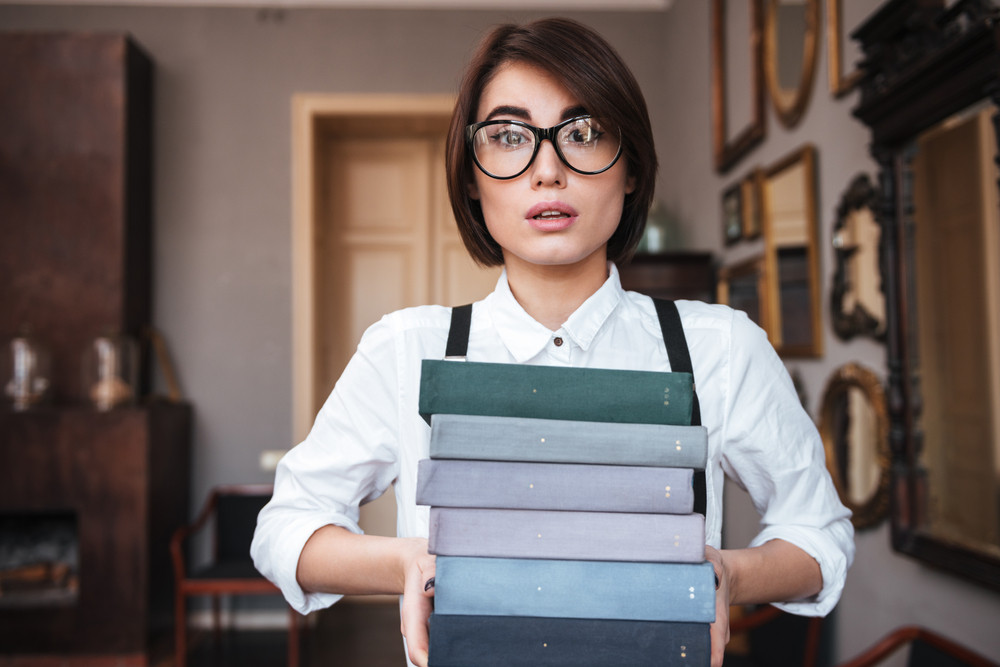 Authoress in glasses and white shirt holding books in hands and looking at camera