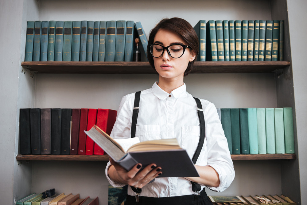 Authoress in glasses and white shirt reading book with bookshelf on background