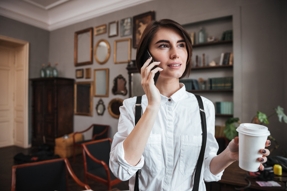 Authoress in white shirt talking on phone and holding cup of coffee