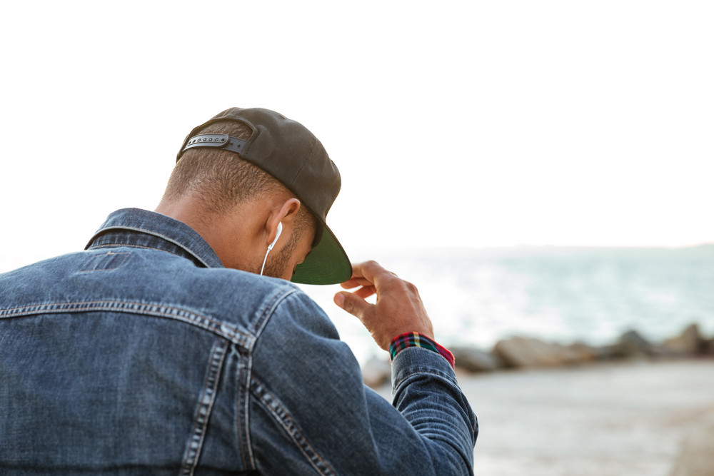 Back view image of handsome african man wearing cap and dressed in jeans jacket looking at beach.