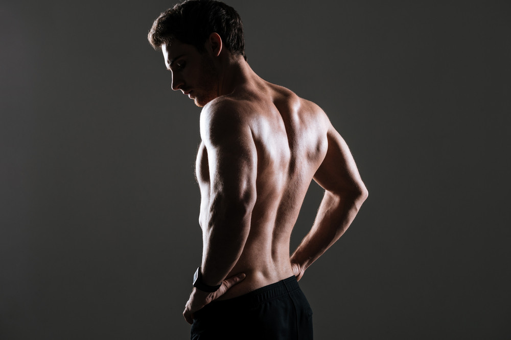 Back view image of handsome sportsman standing in gym over grey background.