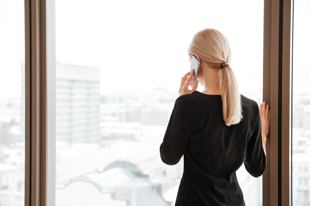 Back view image of young woman worker standing in office while looking at window and talking by her phone.