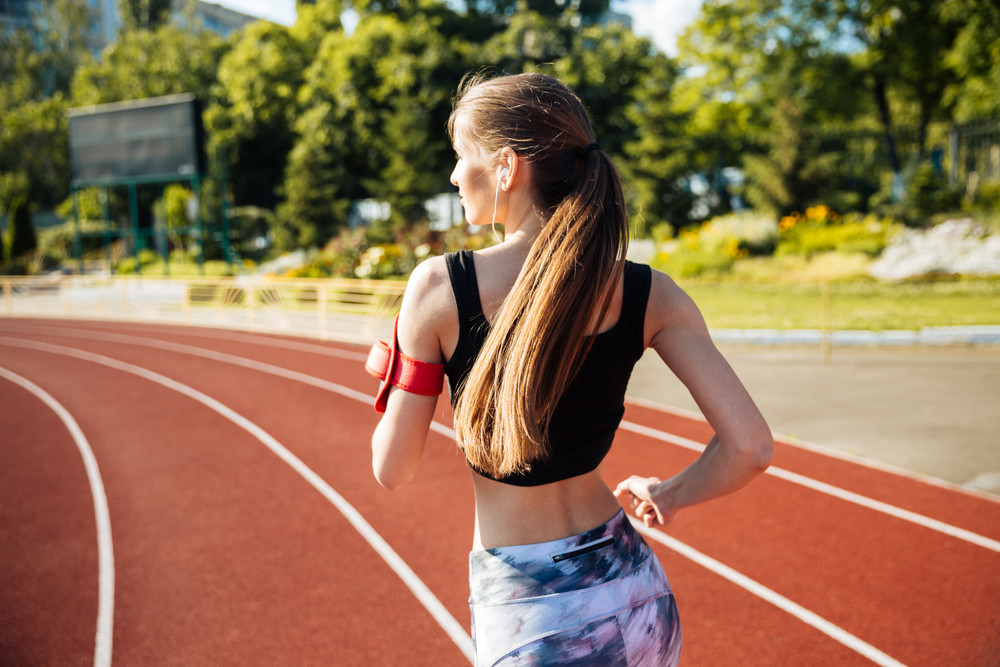 Back view of a female runner listening to music with mobile phone at the stadium