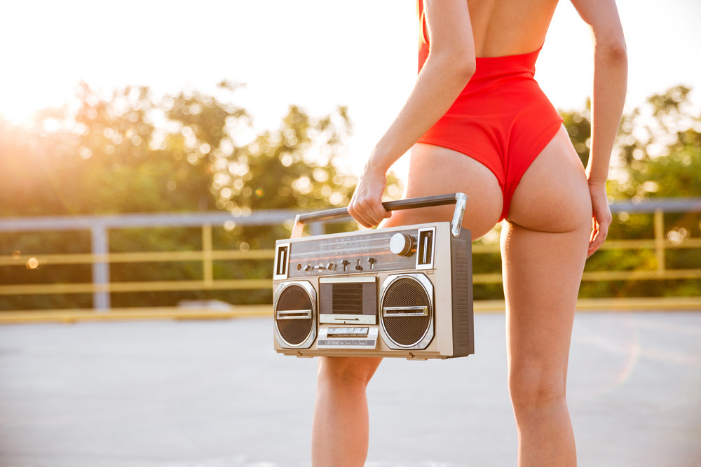 Back view of a girl in red swimsuit on roller skates holding old record player on the open road outdoors