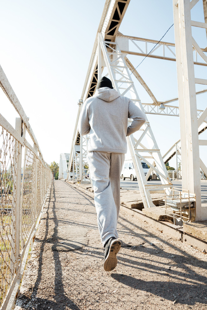 Back view of a jogger in sportswear running along the bridge