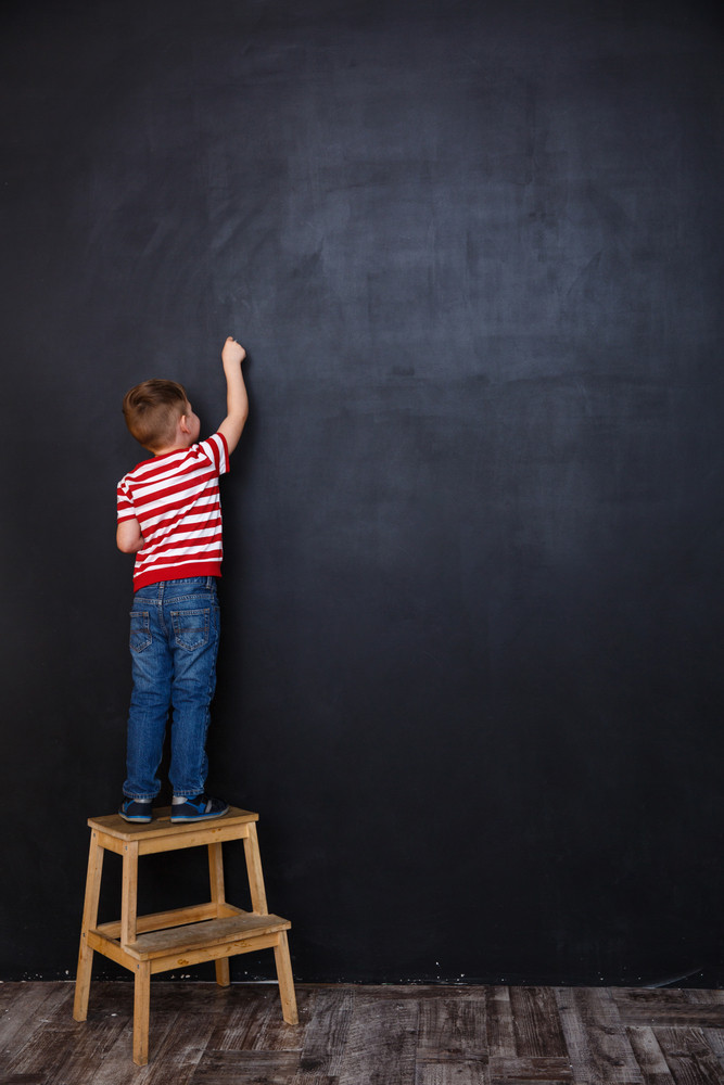 Back view of a little child standing on a chair and drawing on a chalk blackboard
