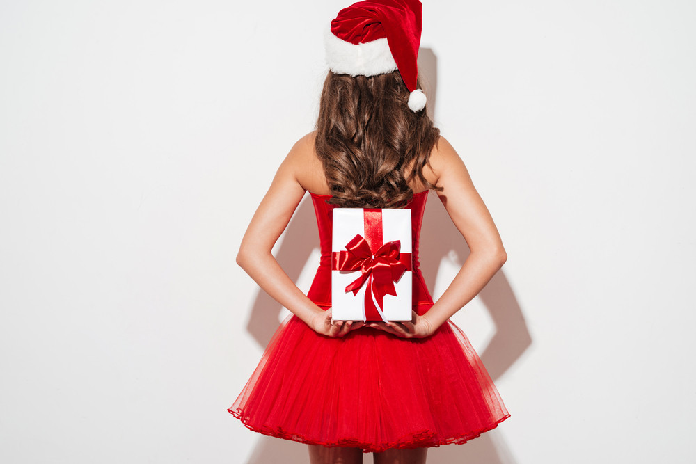 Back view of a young curly brunette woman standing and holding xmas gift box isolated on the white background