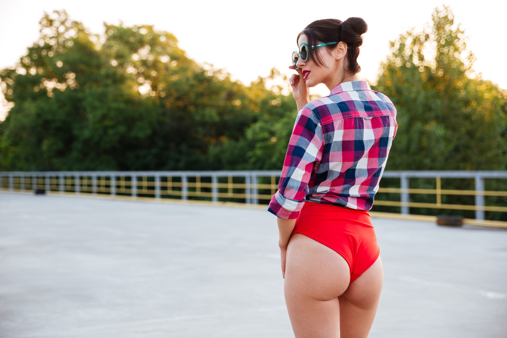 Back view of a young pretty brunette girl in red swimsuit posing on the open road outdoors