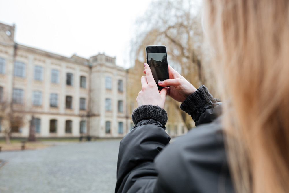 Back view of a young woman taking photo of a beautiful building
