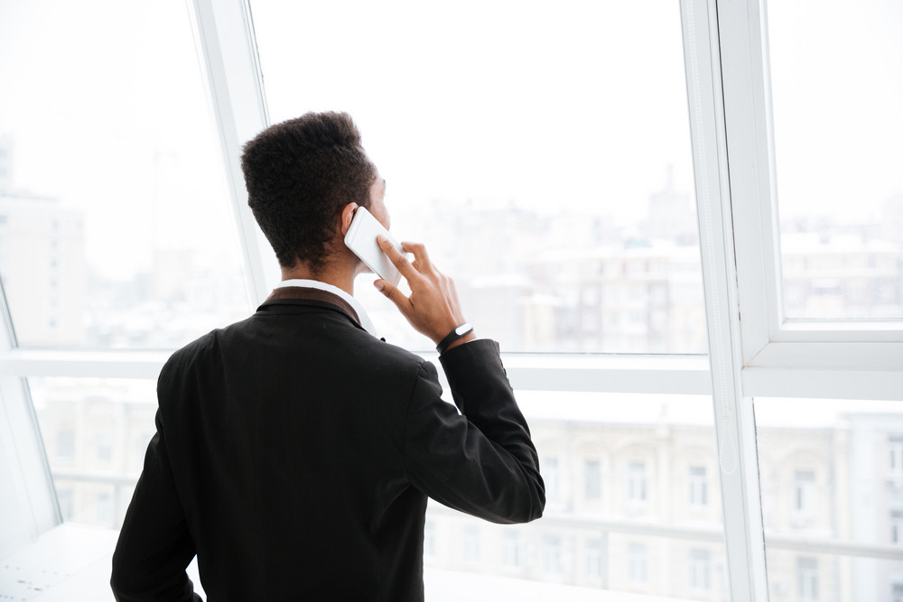 Back view of African business man in black suit talking on phone and standing near the window in office