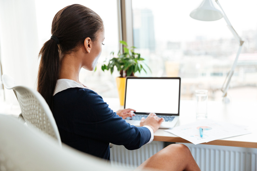 Back view of african business woman in dress sitting by the table in office with laptop