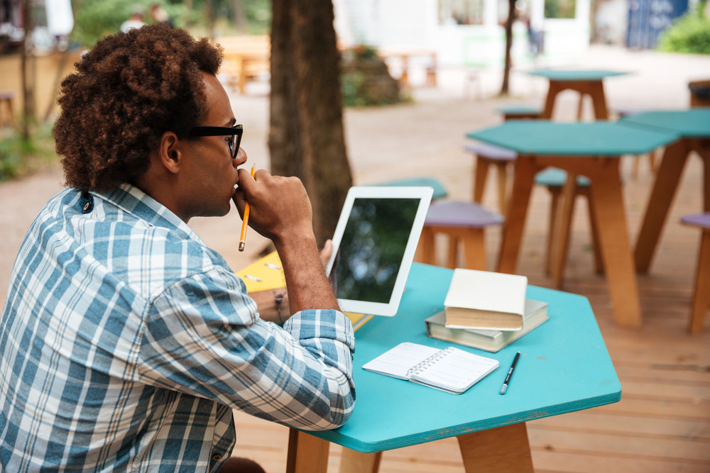 Back view of african young man in glasses studying and using tablet in outdoor cafe