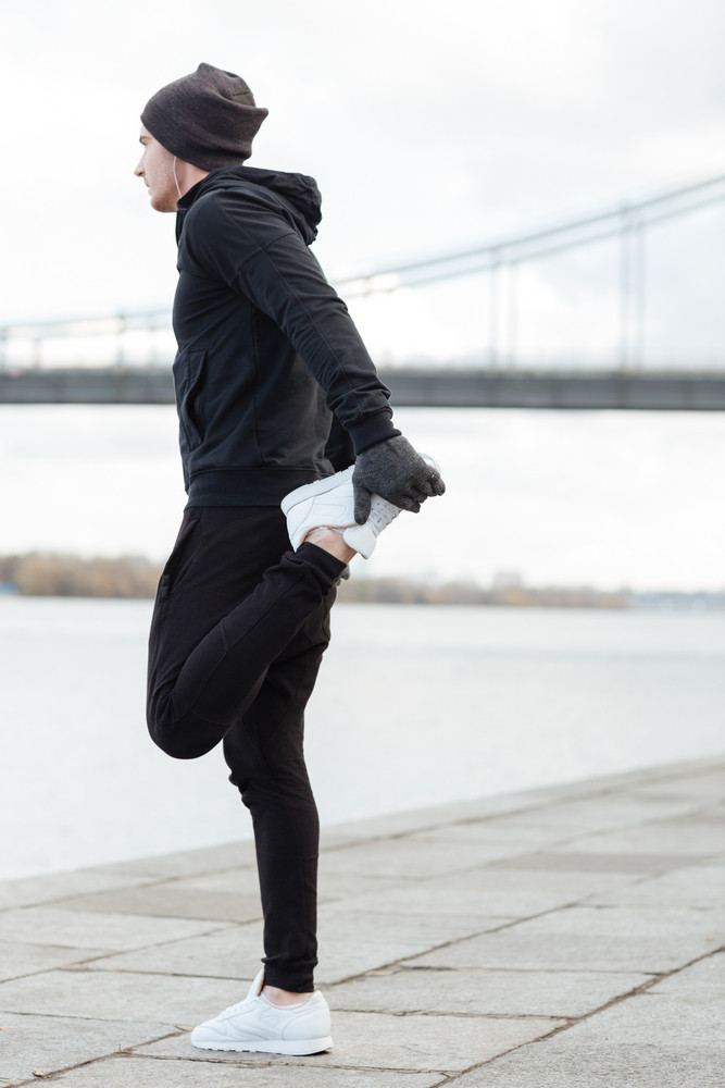 Back view of athletic young man standing and stretching legs outdoors