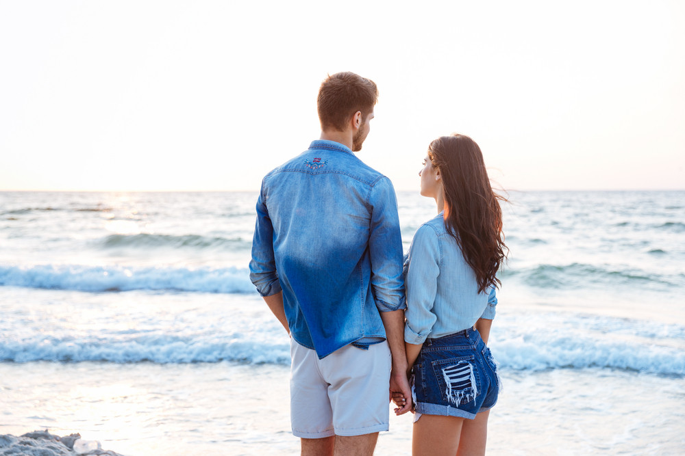 Back view of beautiful young couple holding hands on the beach