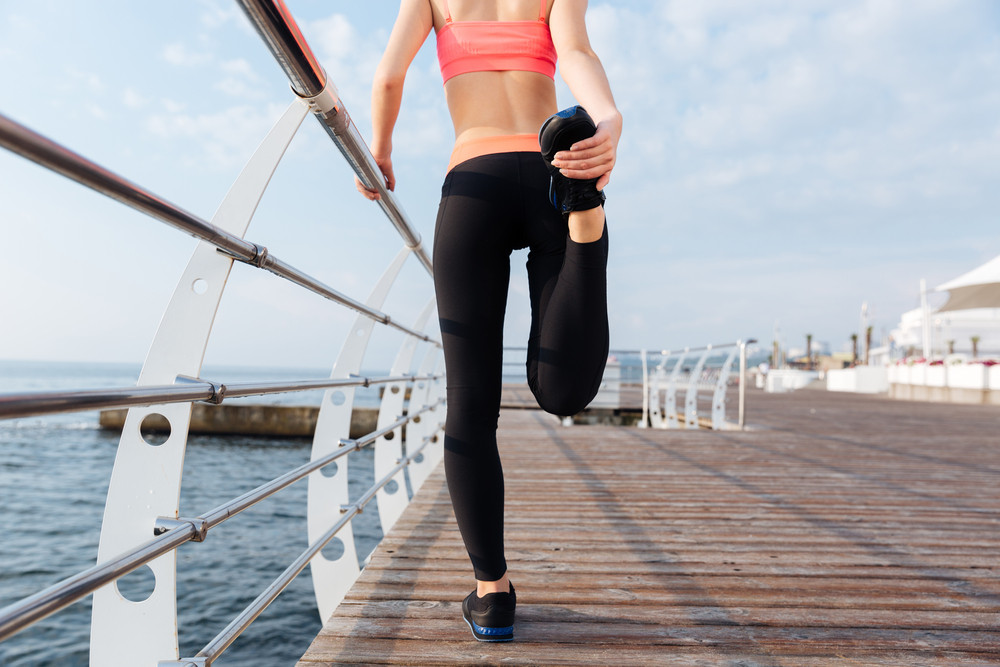 Back view of beautiful young sportswoman stretching legs on pier