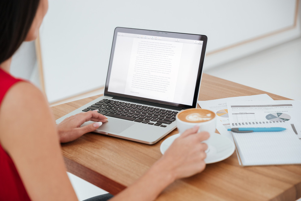 Back view of business woman in red shirt sitting on workplace with laptop, cup of coffee and documents