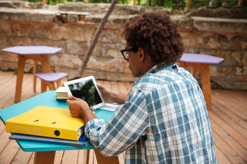 Back view of concenrated african young man sitting and using tablet at the table