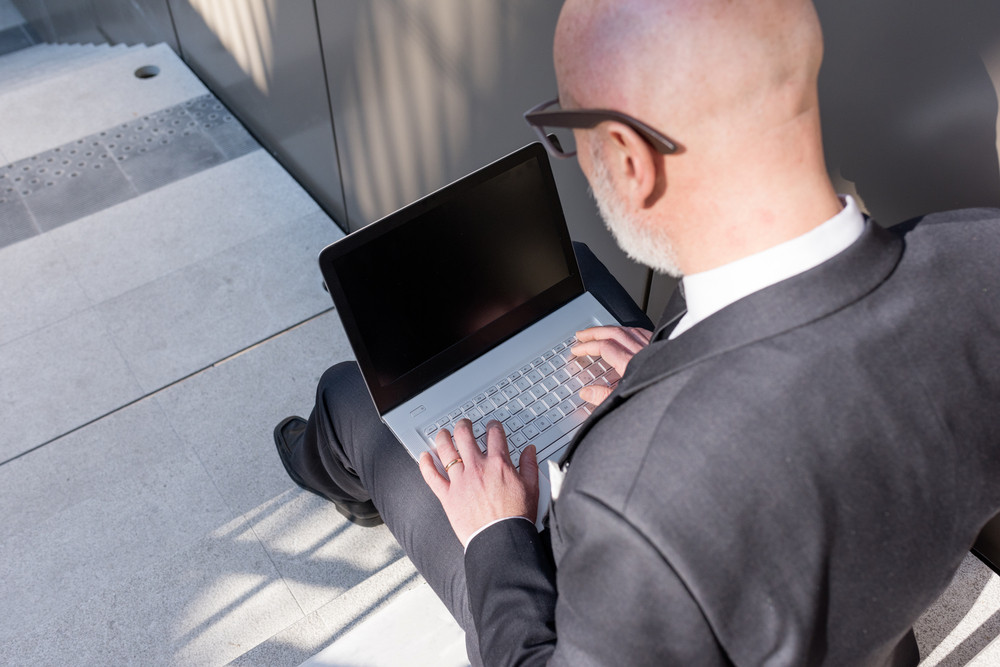 Back view of contemporary middle-age businessman using notebook outdoor in the city - business, technology, communication concept