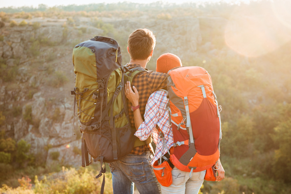 Back view of couple with backpacks in the mountains. cuddling