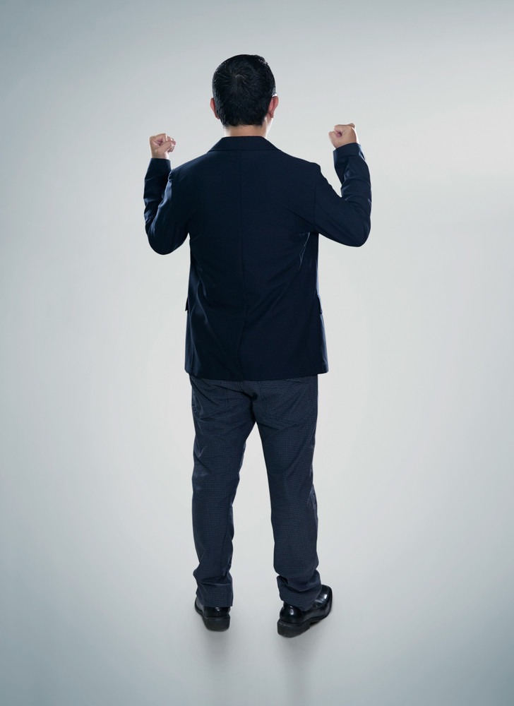 Back view of excited businessman  with arms up