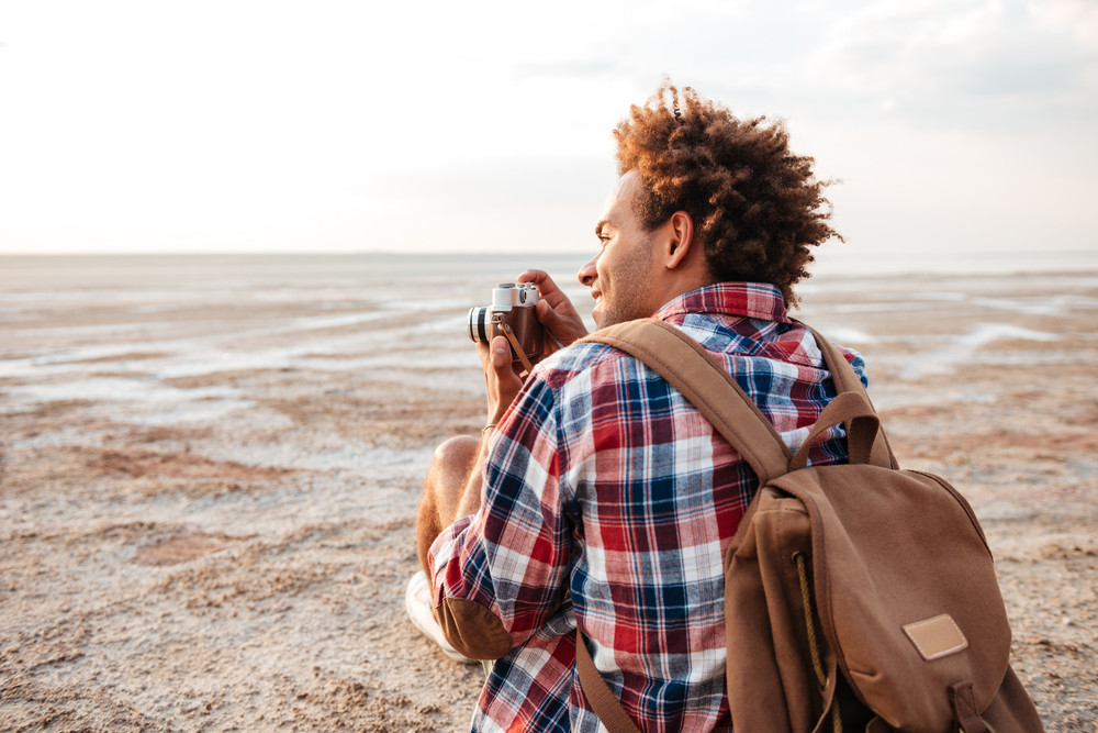 Back view of happy african young man taking pictures on the beach