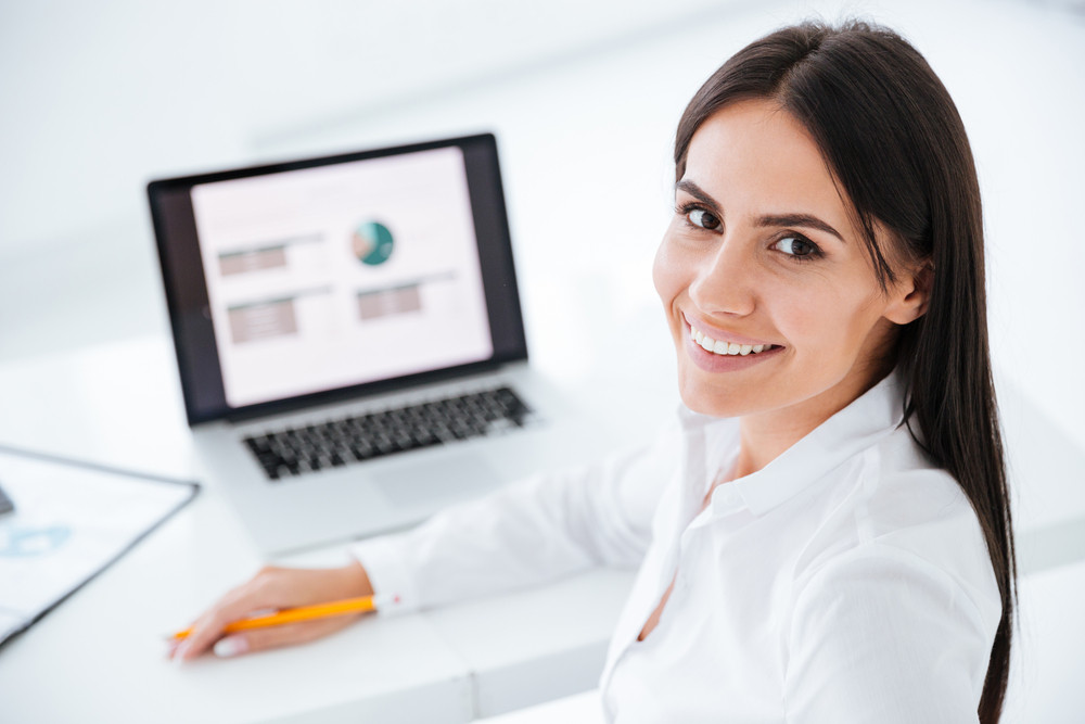 Back view of happy business woman sitting by the table with laptop in office. Close up image