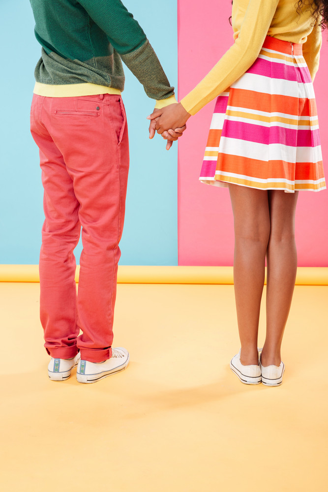 Back view of legs of couple standing and holding hands over colorful background