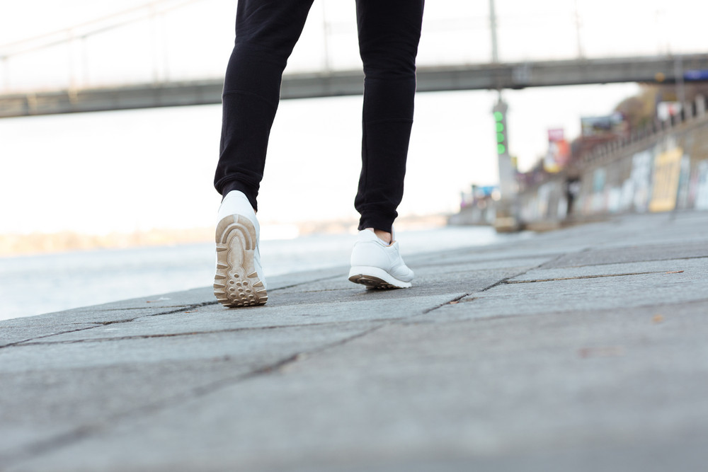 Back view of man athlete legs running outdoors near the river