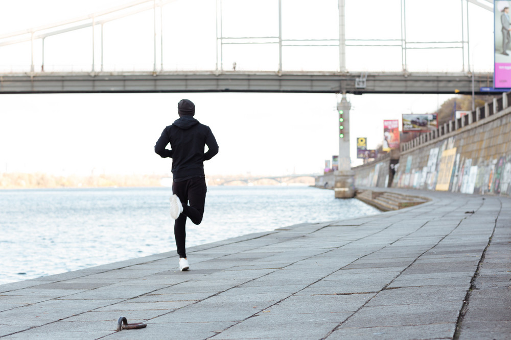 Back view of man athlete running outdoors in autumn