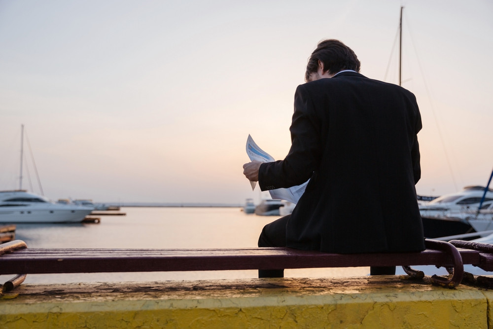 Back view of man in suit with newspaper. in port of Odessa. sitting on a bench