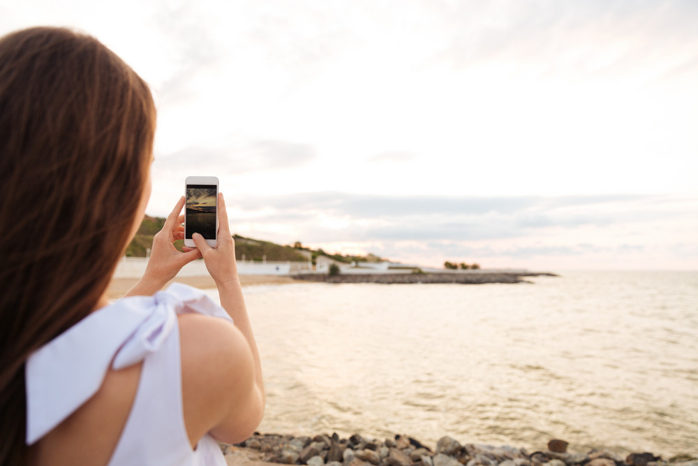 Back view of pretty young woman taking photos with smartphone on the seaside