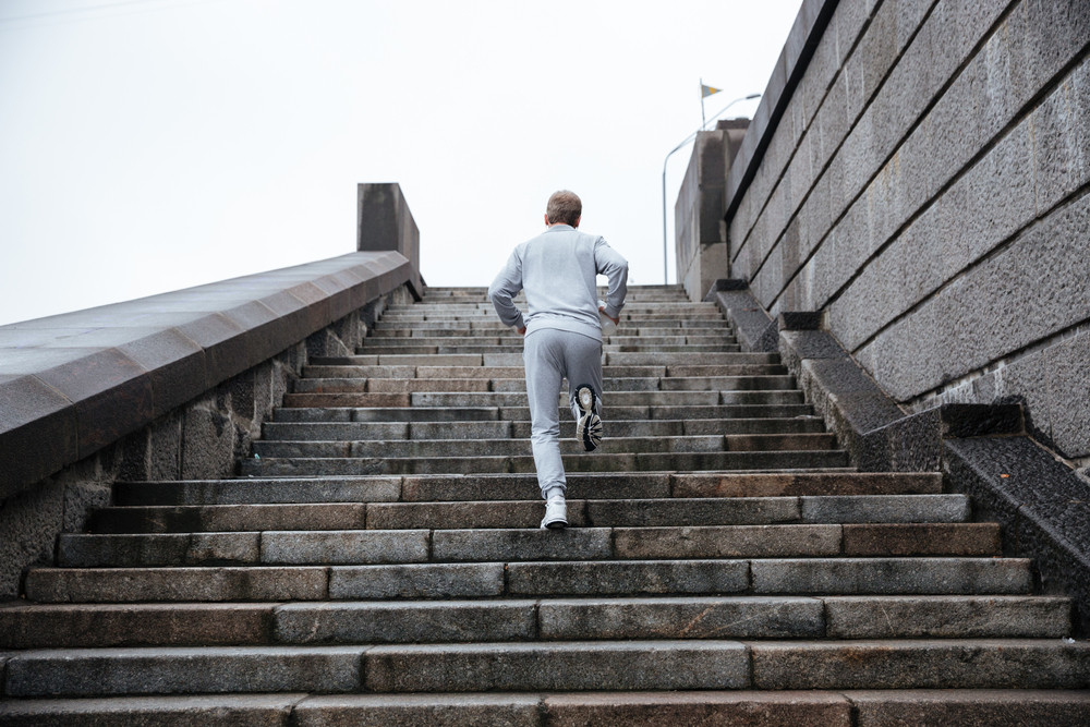 Back view of runner in gray sportswear running on stairs. Full length image