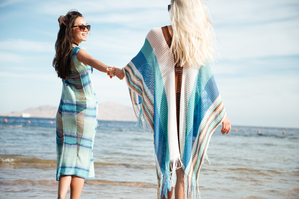 Back view of two young women in beachwear which standing on the beach and holding hands