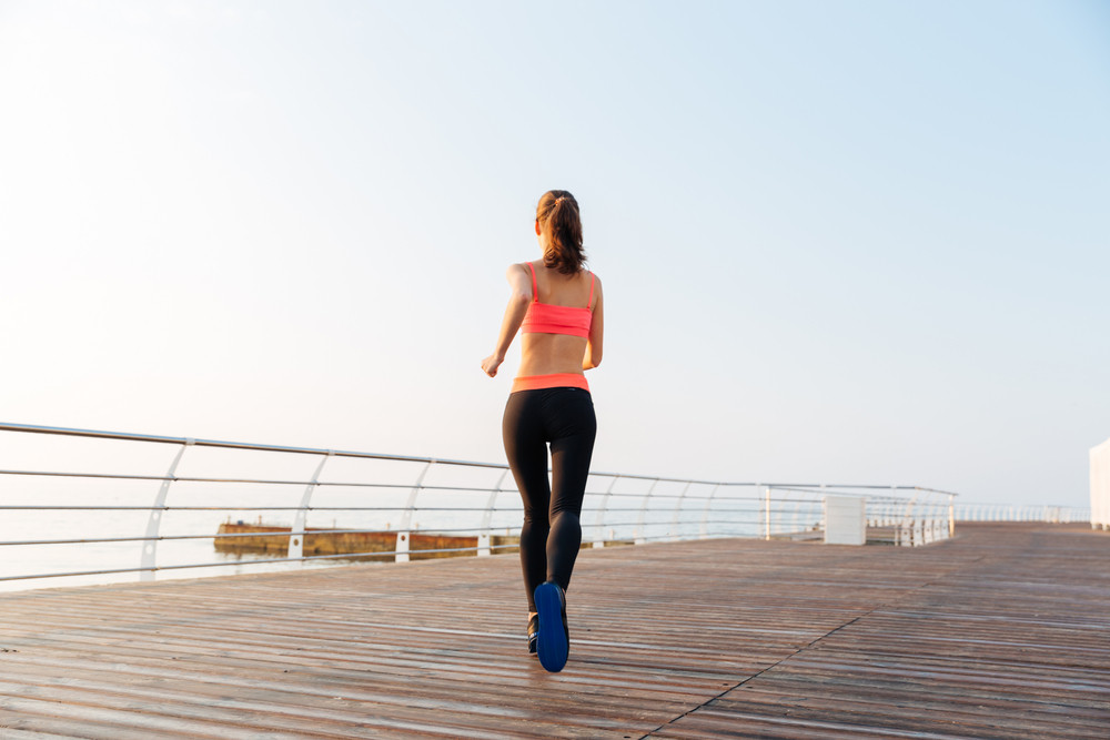 Back view of woman athlete runnig on wooden terrace near the sea