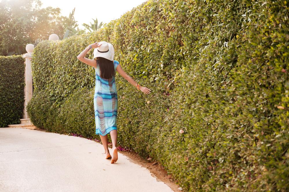 Back view of woman in beachwear which walking near the bush. Full length portrait