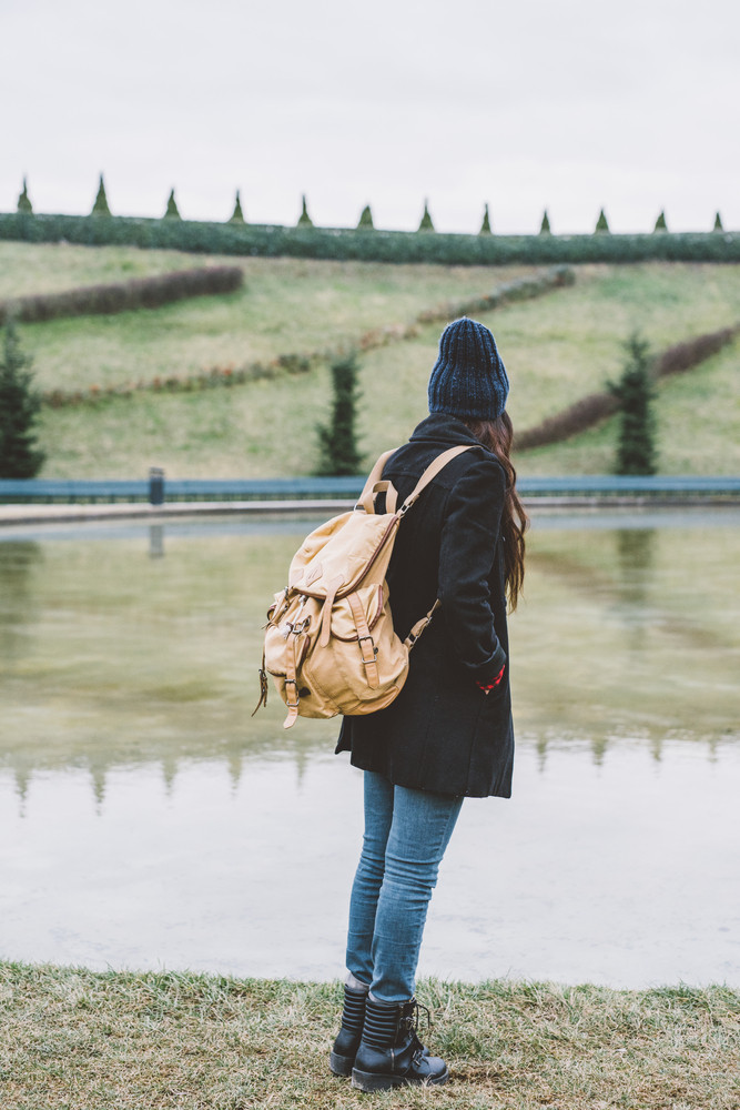 Back view of young beautiful long hair woman with backpack outdoor in city park overlooking, hand in pocket - thinking future, traveler concept