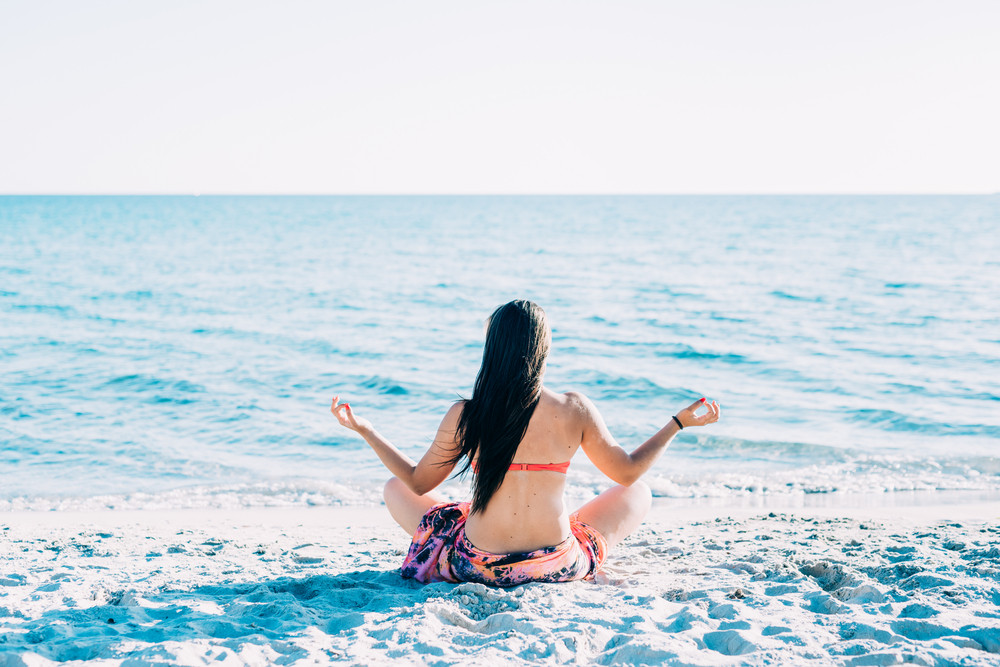 Back view of young beautiful woman doing yoga at the beach in summertime in lotus position- relax, meditation, spiritually concept