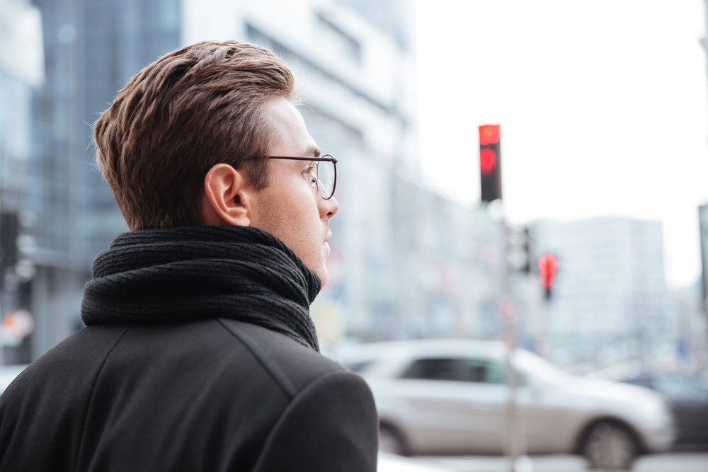 Back view of young business man in glasses and warm clothes standing on the street