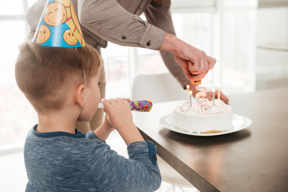 Back view of young father with the birthday cake of his little son.