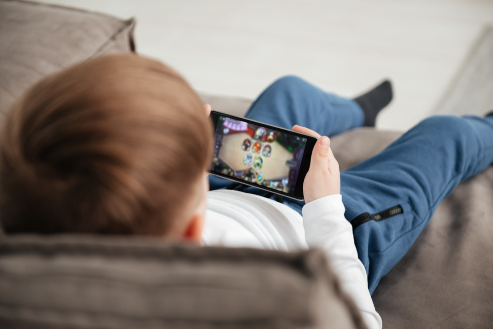 Back view photo of little boy holding smartphone and playing game while sitting on sofa at home. Look at phone.