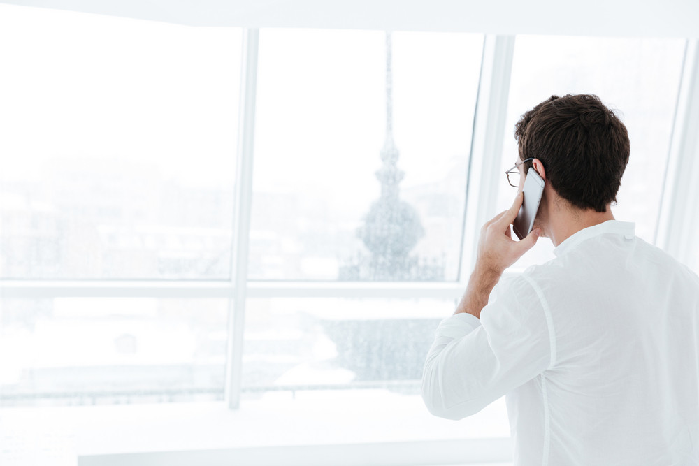 Back view picture of young man dressed in white shirt talking by phone near big white window.