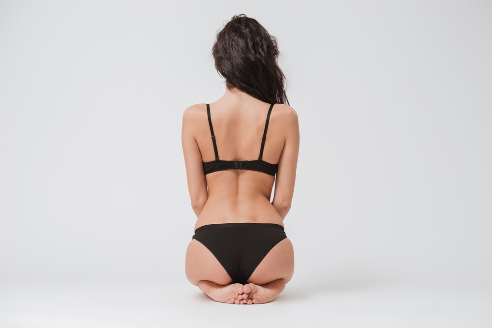 Back view portrait of a young brunette woman in lingerie sitting on the floor on white background