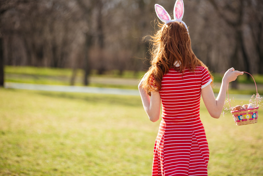 Back view portrait of a young pretty red head woman walking in park with basket and hunting for easter eggs