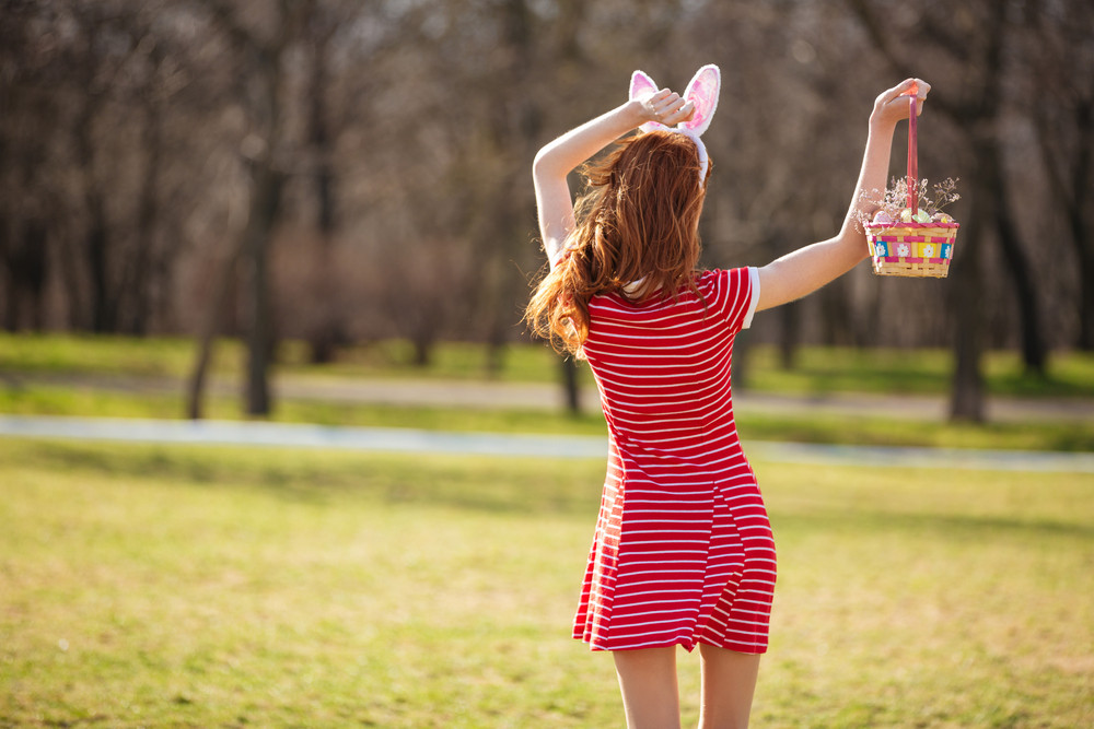 Back view portrait of young red head woman wearing bunny ears and holding easter basket with painted eggs outdoors