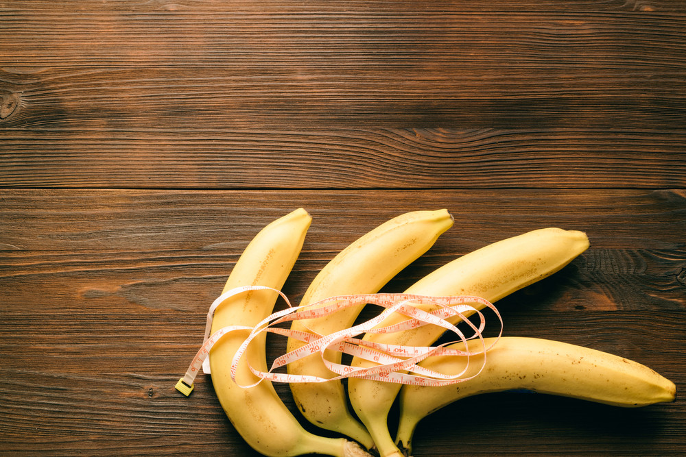 Bananas and measuring tape on a wooden table. Top view, copy space