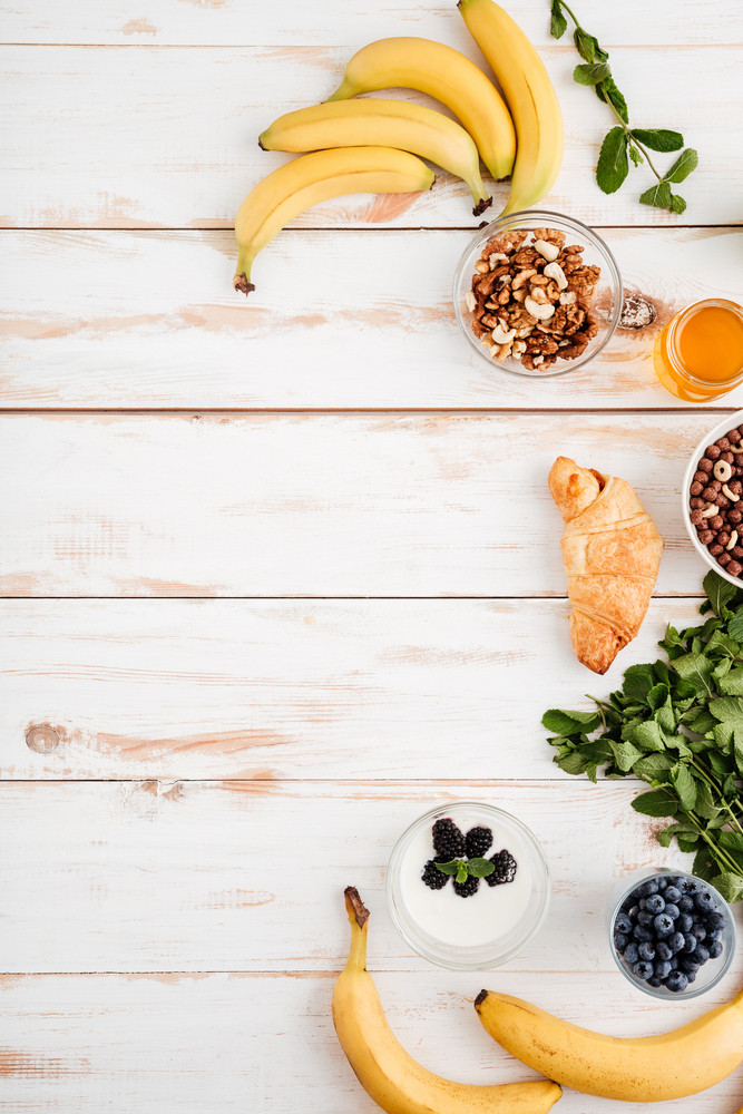 Bananas, berries, croissant, walnuts mint and honey on wooden background